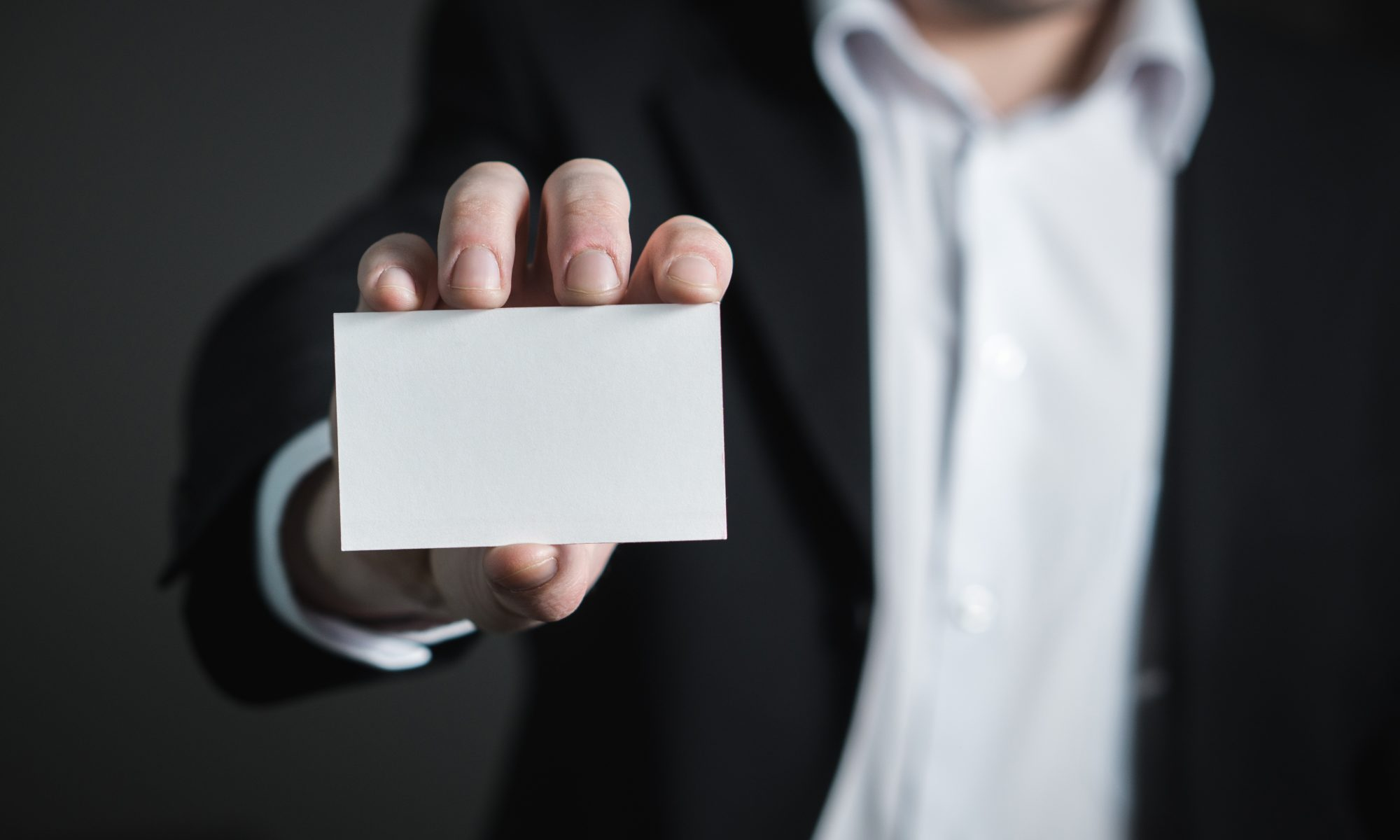 Homme en costume montrant une carte de visite blanche