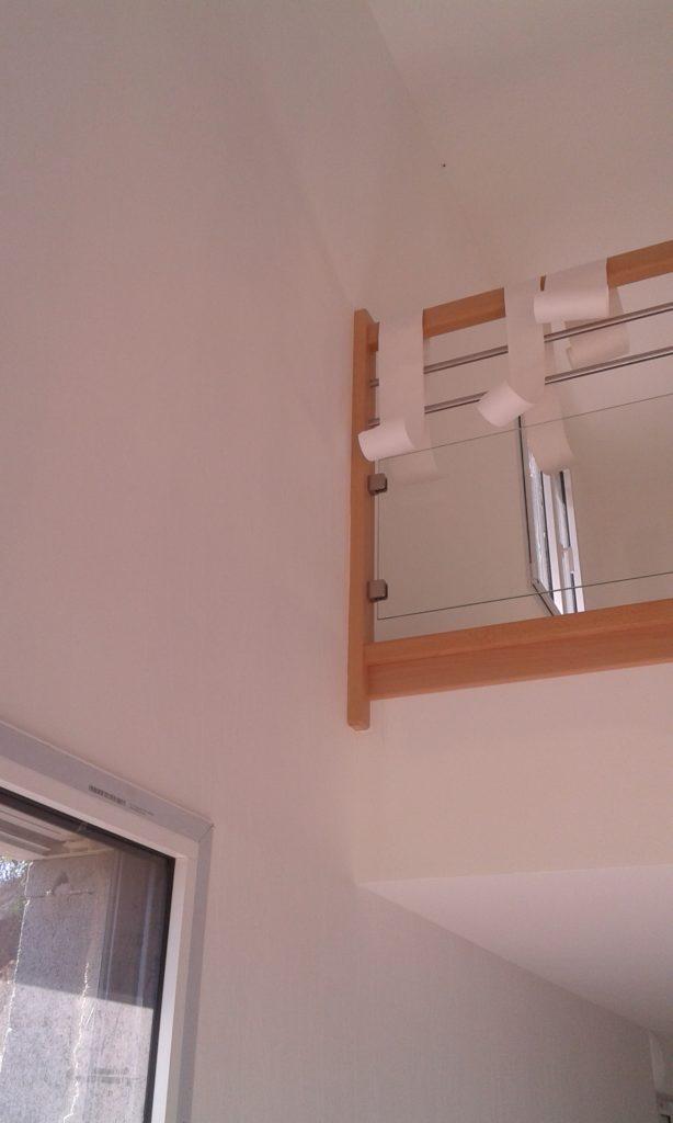 Mur blanc et mezzanine avec bordure en bois, et plaque de verre