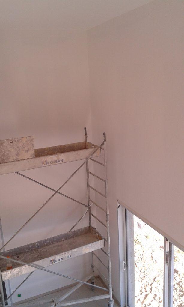 Vue en hauteur donnant sur un angle (avec un échafaudage devant) avec des murs blanc et d'un côté une baie vitrée