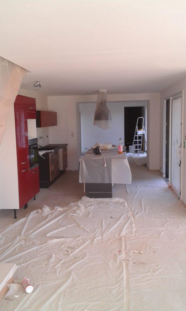 Cuisine au murs blancs avec meubles rouge, marrons et noir