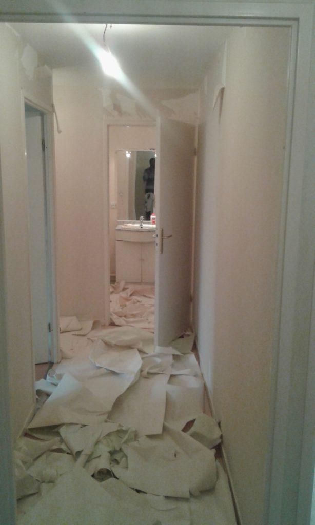 Couloir avec un angle dans lequel on a effectué un début d'arrachage de papier peint