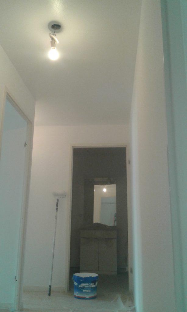 Peinture terminée dans le couloir, avec le pot de peinture et le rouleau de peinture en appuie contre le mur. Reste à enlever les protections et la bâche au sol