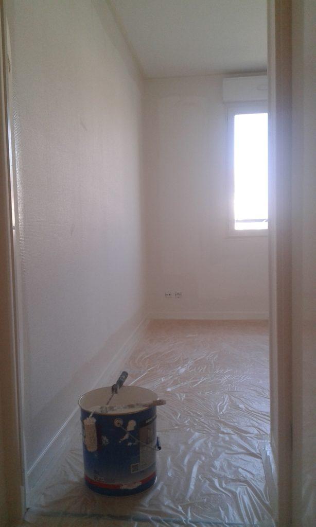 Les angles de la pièce sont peints. Une bâche de protection protège le sol.