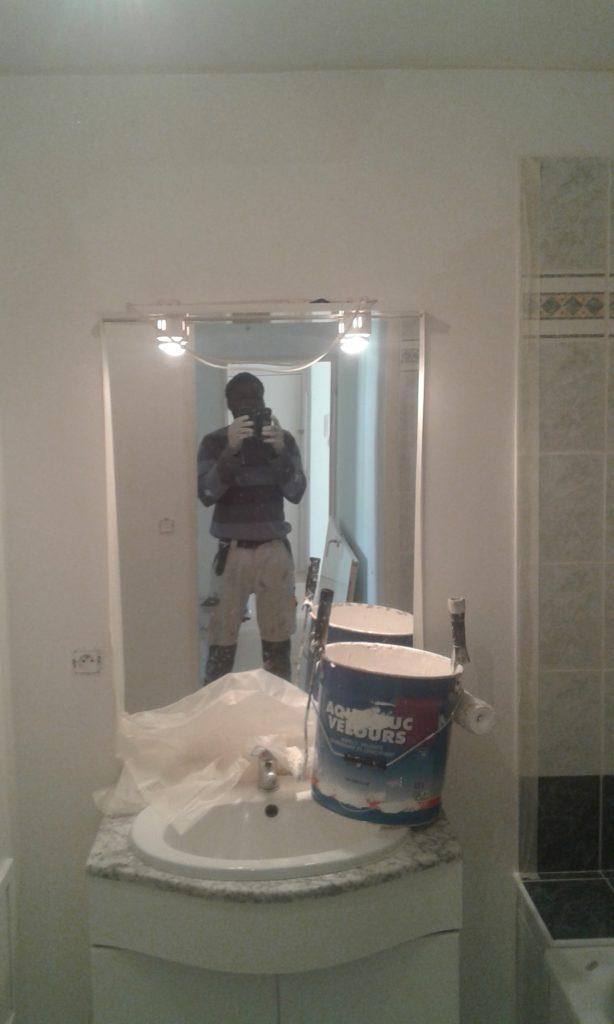 Toile de verre peinte en blanc dans la salle de bain autour d'un meuble (avec évier), d'un mirroir et d'une baignoire