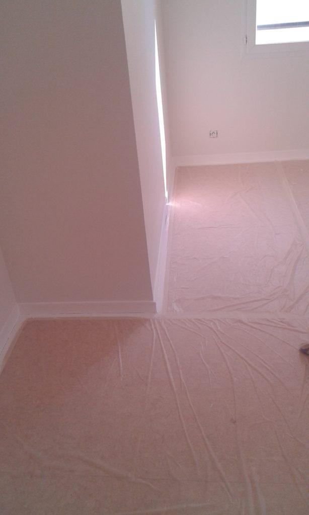 Les murs et les plinthes ont été peintes. Il y a une bâche de protection au sol.