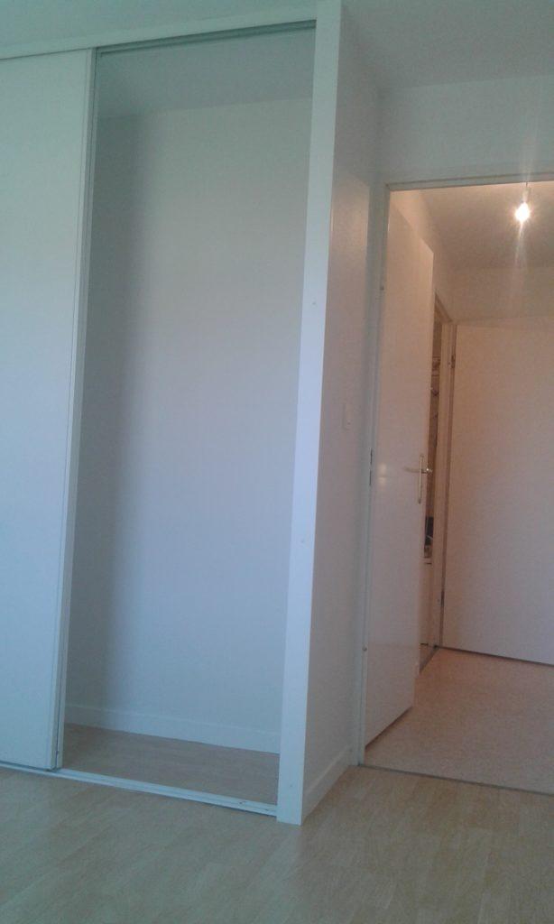 Partie de la chambre avec un placard, sol souple imitation parquet et porte peinte en blanc