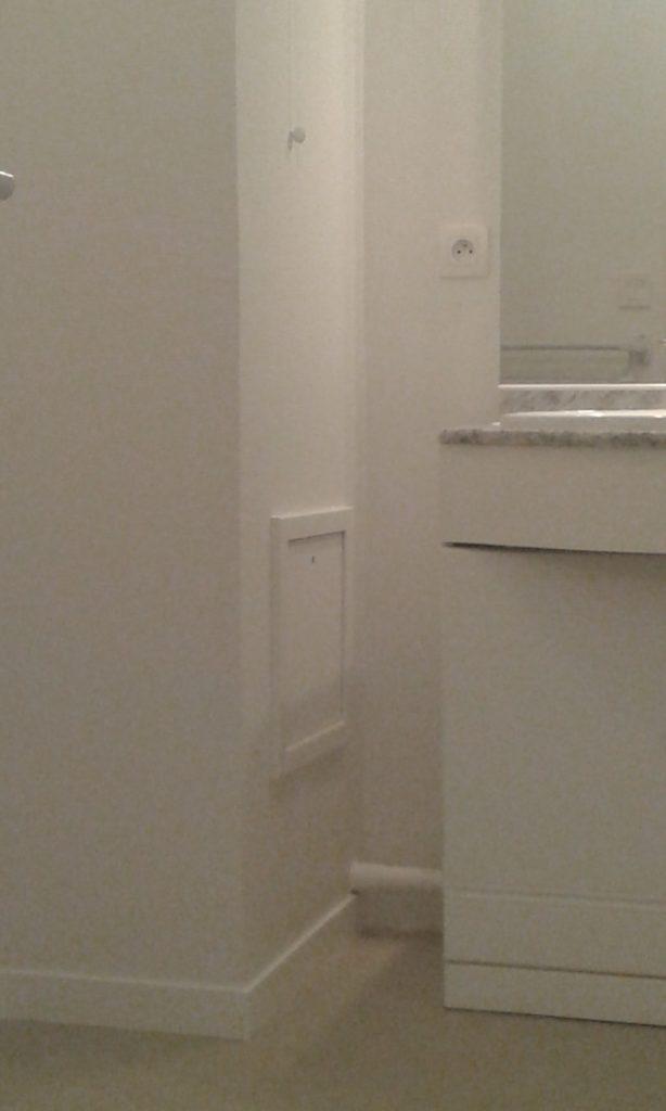 Partie de la salle de bain avec beaucoup d'angles (le mur fait un angle, il y a aussi un meuble avec un mirroir, un tuyau) peint en blanc, après application d'une toile de verre