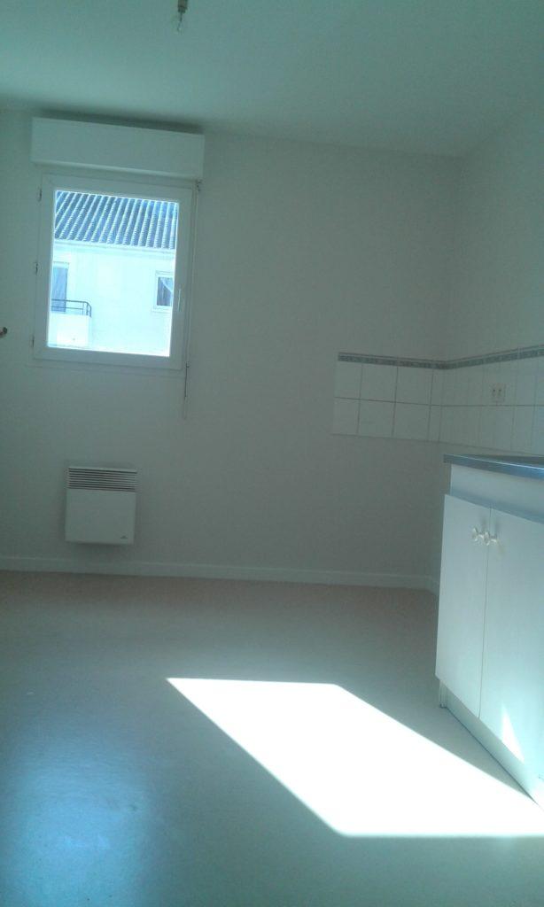 Cuisine (avec un meuble évier, un radiateur et une petite partie du mur carrelée) repeinte en blanc