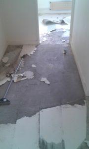 Sol en partie retiré dans un couloir ainsi que dans le commencement de la pièce dans laquelle arrive le couloir