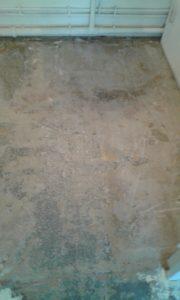 Gros plan sur le sol de la salle de bain qui a été entièrement retiré. Des tyaux passent sur le mur près du sol