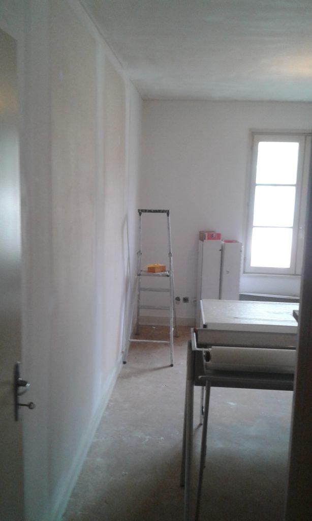 Un mur est peint, l'autre est préparé pour recevoir de la peinture.