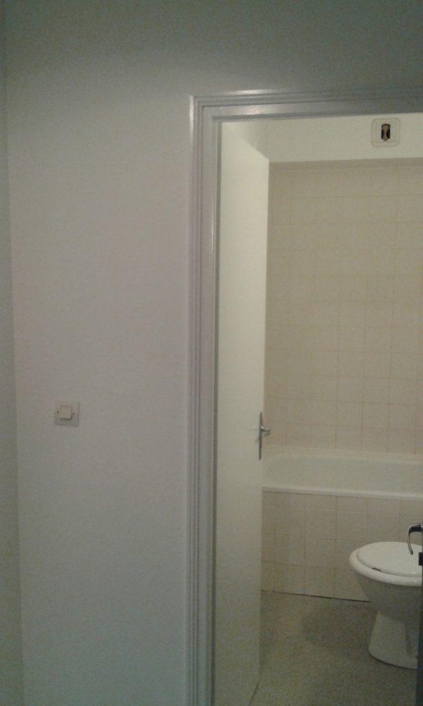 Porte menant à la salle de bain avec un papier peint blanc