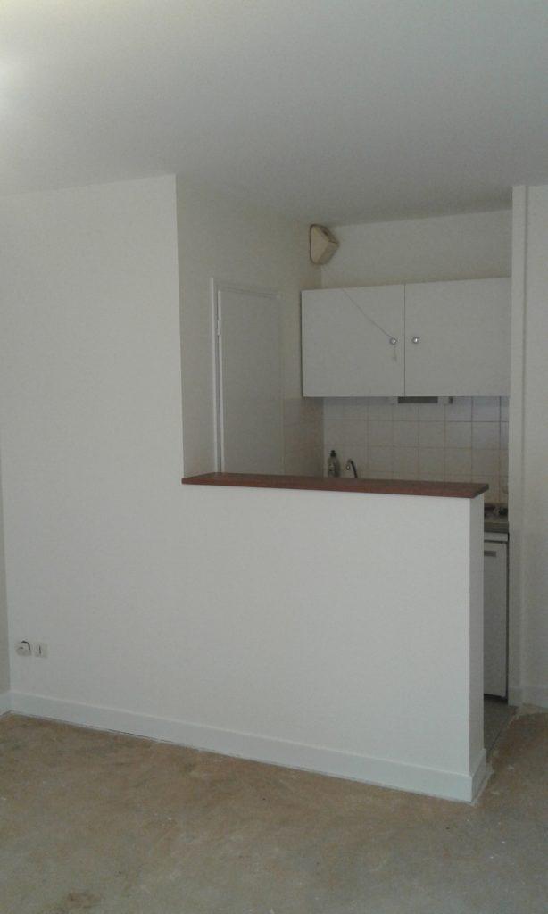 Petite cuisine avec passe plat aux murs et au plafond blancs
