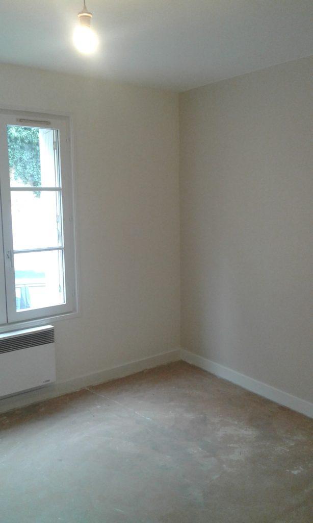Pièce avec fenêtre (volets ouverts) entièrement peinte en blanc.