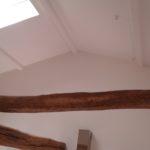 Plafond repeint avec poutres apparentes basses dans la cuisine.