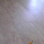 Pose du sol de lames de PVC imitation parquet dans la chambre.